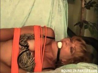 Milf Brandi auf der Couch mit orangefarbenen Seilen gebunden