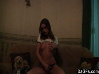Skinny Brunette Teen Striptease im Wohnzimmer.