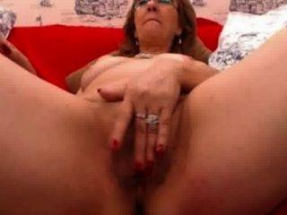 reife Frau mit Brille spielt mit ihren haarigen Pussy