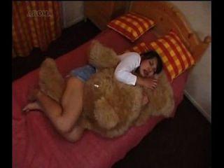 japanisches Mädchen, das einen Teddybären humpelt reiben