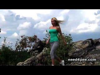 sportliche Blondine runter für eine Pisse auf den Felsen