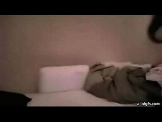 schöne indische Frau mit langen schwarzen Haaren in ihrem Gewand sitzt auf einem Bett