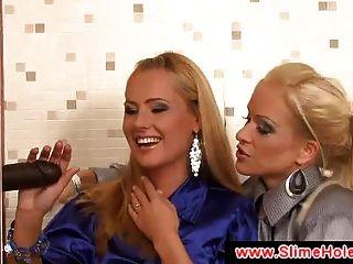 zwei Blondinen schwarzen Schwanz durch ein Glory Hole saugen