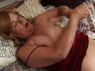 alte reife Hausfrau auf ihrem Bett spielen