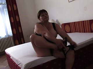 vollbusigen Mama spielen auf ihrem Bett