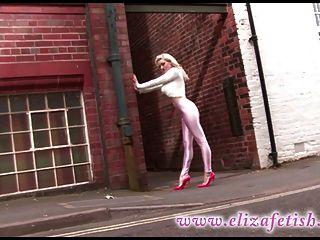 heiße Blondine trägt rosa Disco-Hosen und jimmy choos.