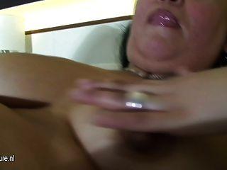 reife Schlampe Mutter mit einem Dildo auf ihrem Bett spielen
