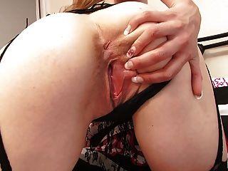 kurvige junge Blondine schaut in sexy Spitze und Strümpfe atemberaubenden