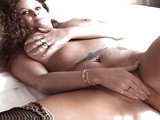 sexy Rotschopf auf dem Bett spielt mit ihrer Pussy