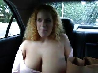 vollbusige Rothaarige zeigt auf dem Rücksitz eines Autos ihre Brüste