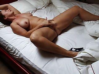 schöne, reife Frau im Bett masturbiert