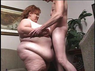 grotesk fettleibiges weißes Küken wird von einem dünnen Kerl titbiert