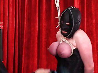 corseted gefesselte Frau in Leder Kapuze bekommt Titten gebunden, so dass sie rot werden
