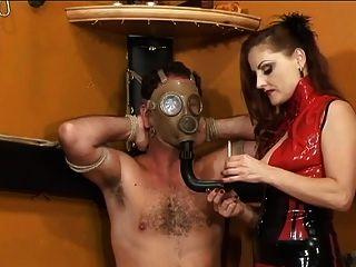 sexy dominatrix im roten kleid verbrennt Sklave mit rauchender Zigarette im Kerker