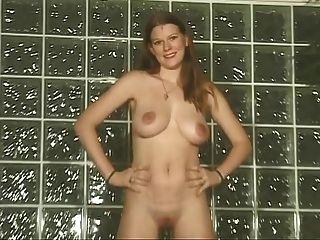 Mädchen gegen Wand zeigt ihre großen Titten und rasierte Muschi