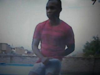 schwarzer Kerl auf dem Dach reibt seine riesige Ausbuchtung