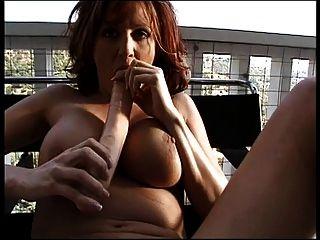 busty redhead fickt ihre Pussy mit doppelköpfigem Dildo auf hohem Holzbalkon