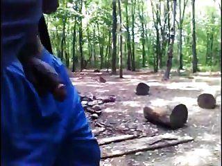schwarzer Kerl geht im Wald mit Hahn aus