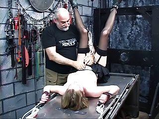 niedliche junge Blondine mit durchbohrten Brustwarzen aufgehängt auf den Kopf in bdsm lair