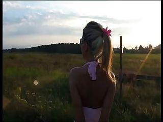 posiert in rosa Kleid und rosa 7 offene Zehe High Heel Sandalen