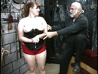 Junge BDSM Sklavin Mädchen Brünette im Korsett ist verprügelt und im Keller gekämmt