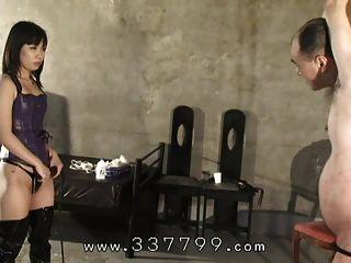 japanische Domina hängt einen Sklaven und trifft eine Peitsche.