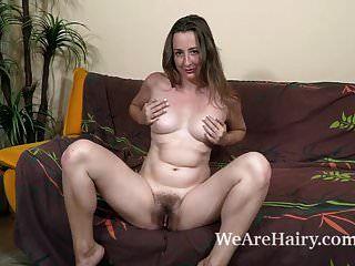 lucia siberia zieht sich nackt auf ihrer braunen couch aus