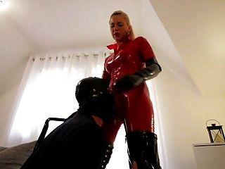 Schlampe in rotem Latexkatzenanzug schwarze Stiefel fickt Sklave