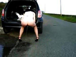 Frau pinkelt durch das Auto